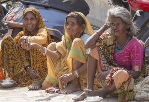 Beggars indian women waits for alms on a street in Pushkar, India